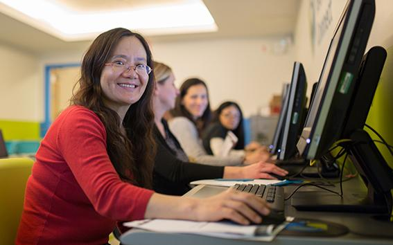 Woman smiling towards camera while using a computer