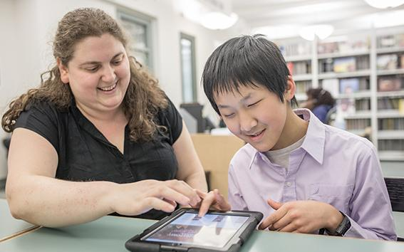 Librarian helping a young man with a tablet computer.