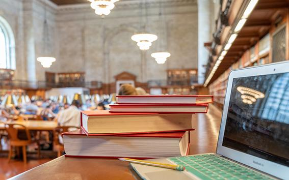 Computer and a stack of books.